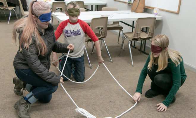 The youth trying to make a square with the rope while blindfolded