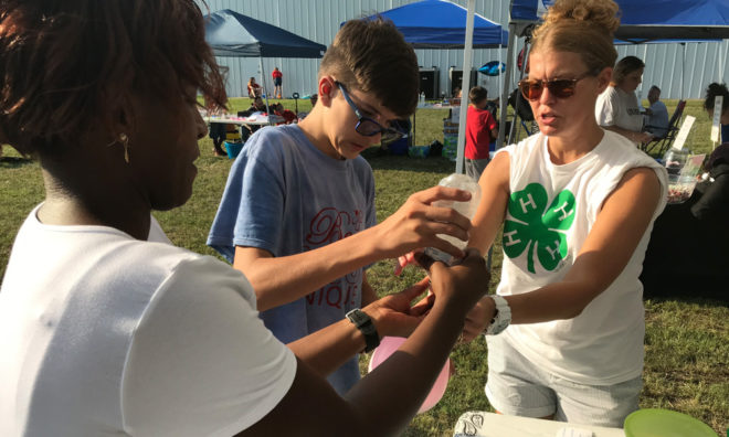 Youth pouring rice into balloon for stress ball