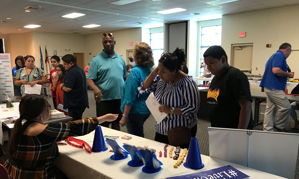 Attendees visit a booth of a local organization
