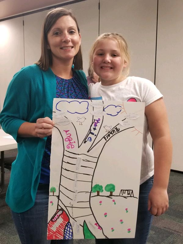 Parents and youth show off the family trees they constructed.
