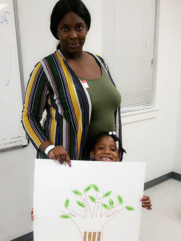 Youth and caregiver hold poster