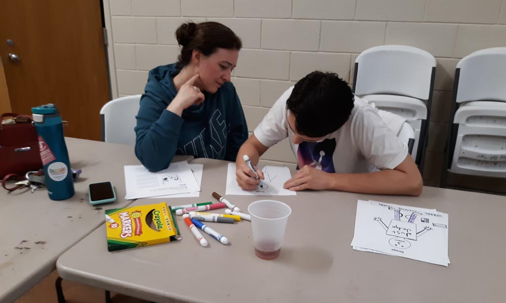 Youth helping caregivers draw an image of themselves.