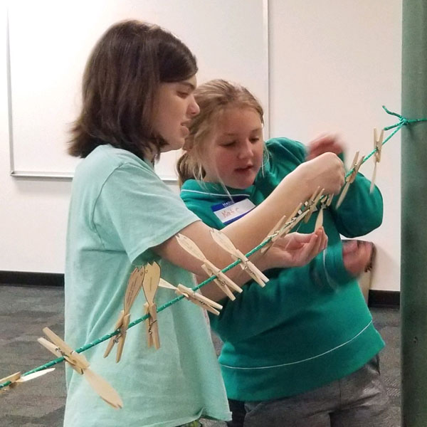 Youth work together for an activity involving clothes pins.