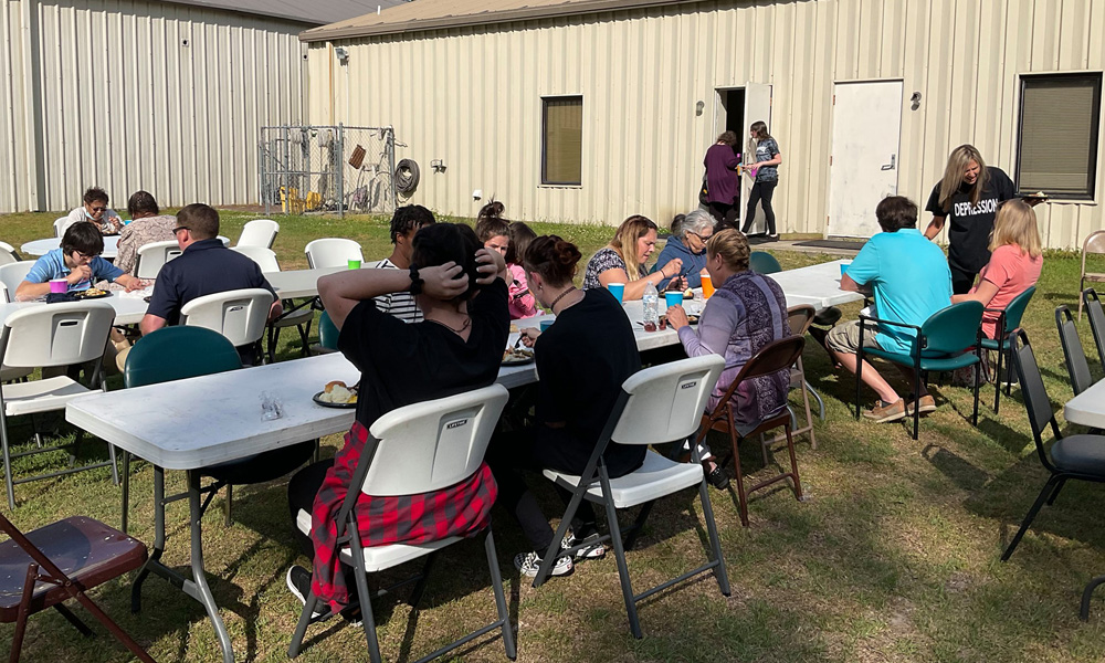 Attendees eat dinner outside on the lawn