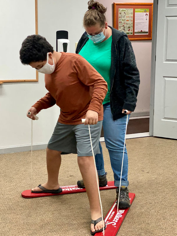 Caregiver and youth participant working on cooperation and teamwork with the walking boards